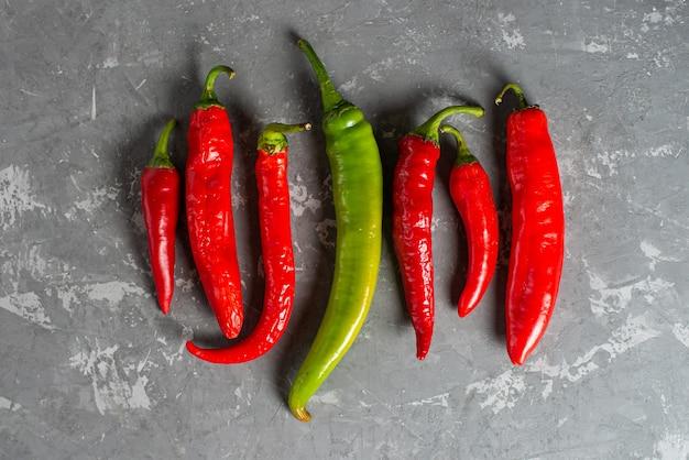 Frische chilischoten von roter und grüner farbe gleichmäßig auf einem konkreten hintergrund ausgelegt.