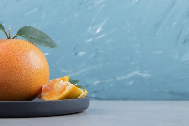 Frische clementine und segmente auf schwarzem schneidebrett.