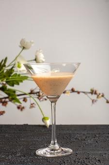 Frische cocktails der vorderansicht mit blumen auf grauer oberfläche
