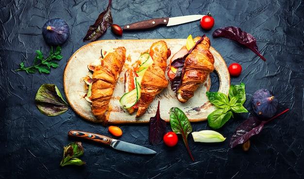 Frische croissants, gesundes frühstück. croissants mit forelle, fleischspeck, gemüse und obst