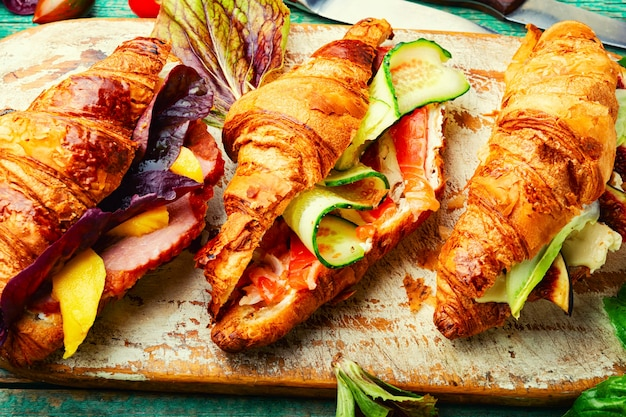 Frische croissants mit gesalzener füllung.croissants mit forelle, fleischspeck, gemüse und obst