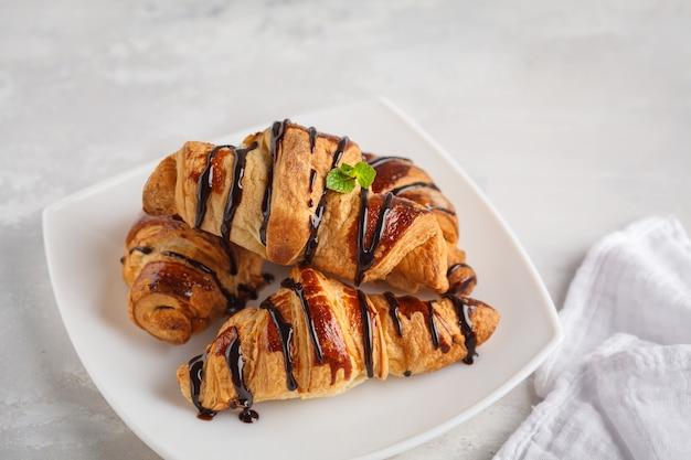 Frische croissants mit schokoladensirup auf hellgrauem hintergrund, kopienraum. dessertkonzept der französischen küche.