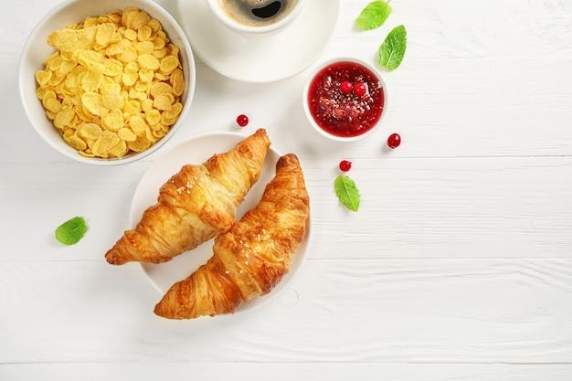 Frische croissants, schwarzer kaffee, müsli und marmelade auf weißem holz.