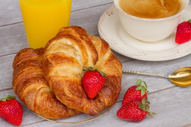 Frische croissants und frische erdbeeren auf dem tisch