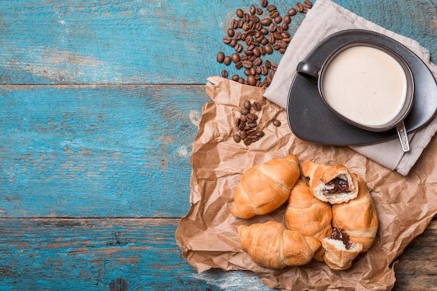 Frische croissants und kaffee auf holztisch