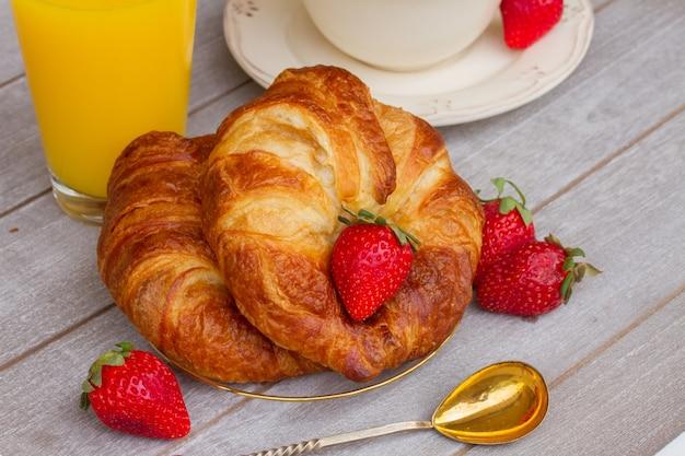 Frische croissants und rote erdbeeren auf dem tisch