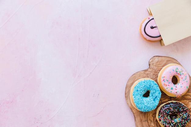 Frische donuts auf schneidebrett in der nähe von paket über rosa hintergrund