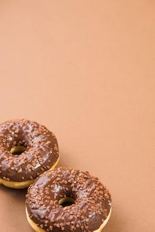Frische donuts mit dunkler schokoladenüberzug und streusel