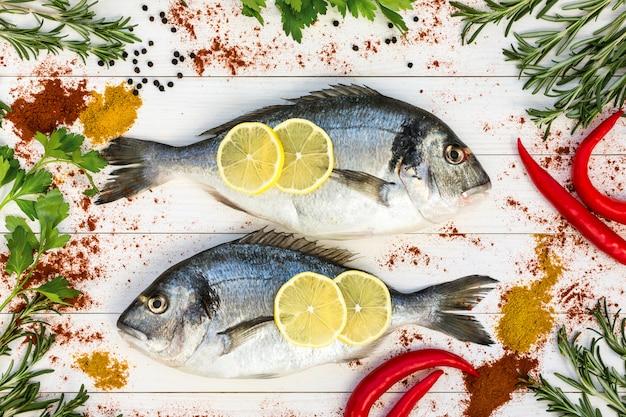 Frische doradofische, rosmarin und gewürze herum auf weißem holztisch.