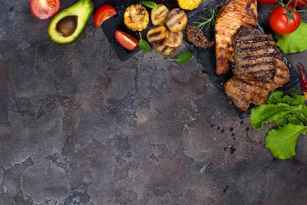 Frische drei arten gegrilltes steak auf schieferplatte mit kräutern, tomaten, avocado und gegrillten kartoffeln