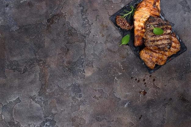 Frische drei arten gegrilltes steak (huhn, schweinefleisch, rindfleisch) auf schieferplatte mit kräutern
