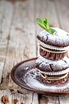 Frische dunkle schokoladenmuffins mit zuckerpulver und minze treiben auf brauner platte blätter