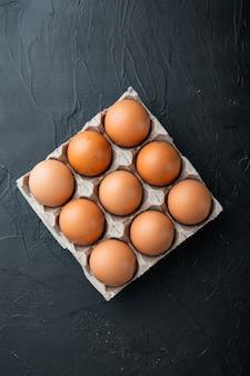 Frische eier auf papier eierkartonsatz, auf schwarzem hintergrund, draufsicht flach legen