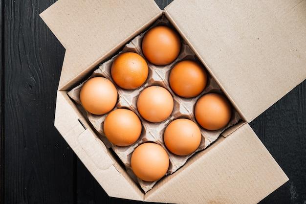 Frische eier auf papier eierkartonset, auf schwarzem holztisch
