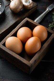 Frische eier auf papier eierkasten gesetzt, auf alten dunklen holztisch hintergrund