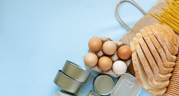 Frische eier, brot und milchprodukte in aluminiumbehältern flaylay auf blauem hintergrund