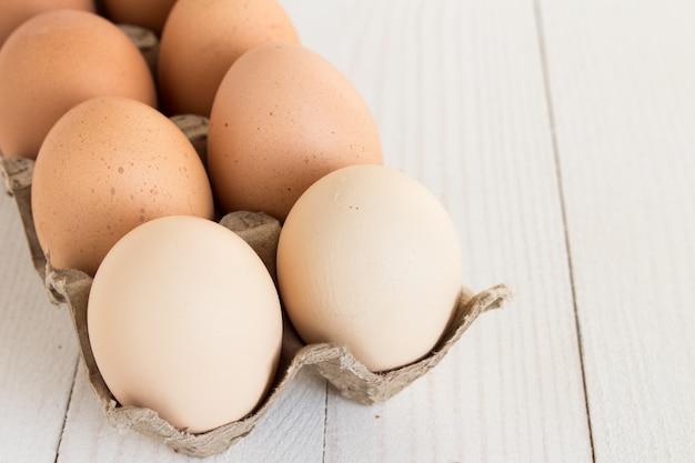 Frische eier im kartonpaket auf weißem holz