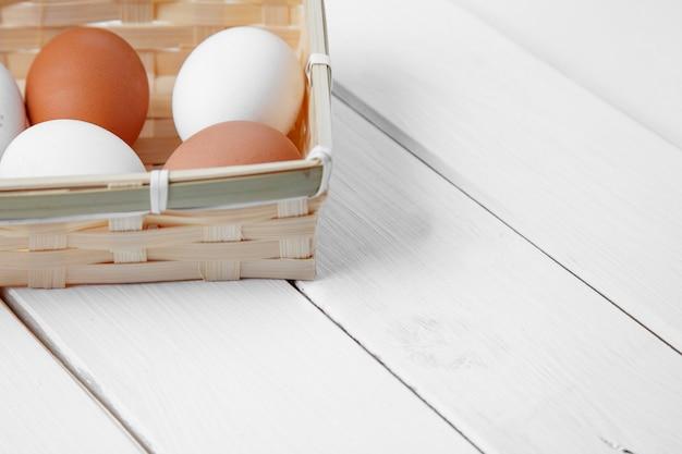 Frische eier in einem korb auf einem hölzernen hintergrund.