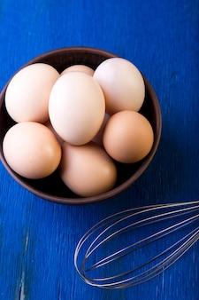 Frische eier in einer braunen schüssel auf blauer oberfläche, draufsicht