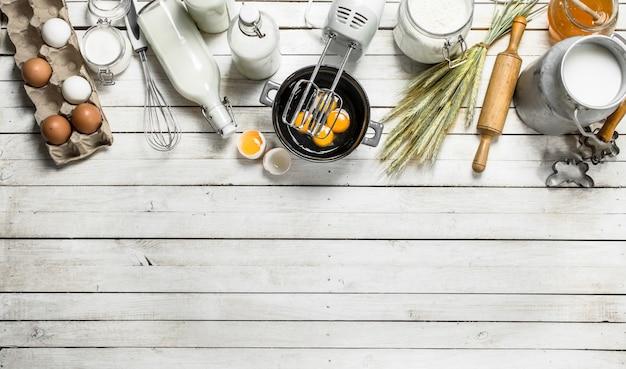Frische eier mit einem mixer auf weißem holztisch.