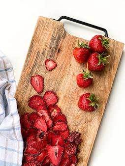 Frische erdbeer- und getrocknete erdbeerscheiben auf holzbrett. speicherplatz kopieren. draufsicht.