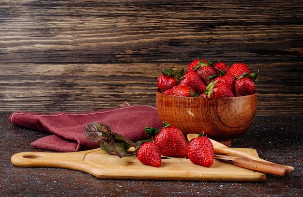 Frische erdbeere der seitenansicht mit basilikum und brett auf hölzernem hintergrund