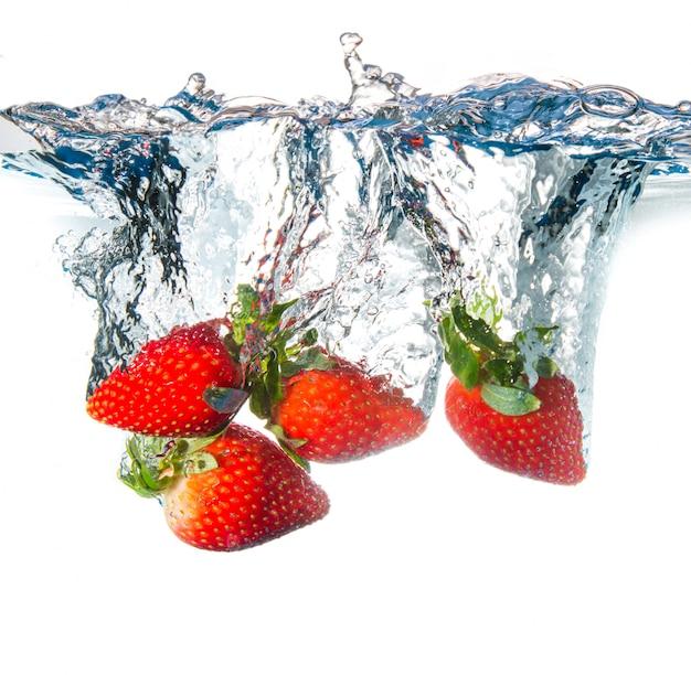 Frische erdbeere, die in wasser fällt