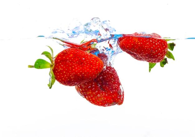 Frische erdbeere fiel in wasser mit spritzen auf weißen hintergründen
