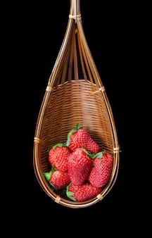 Frische erdbeere in einem hölzernen korb lokalisiert auf schwarzem hintergrund