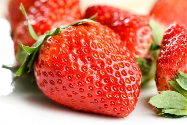 Frische erdbeere und blätter der nahaufnahme lokalisiert auf holztisch