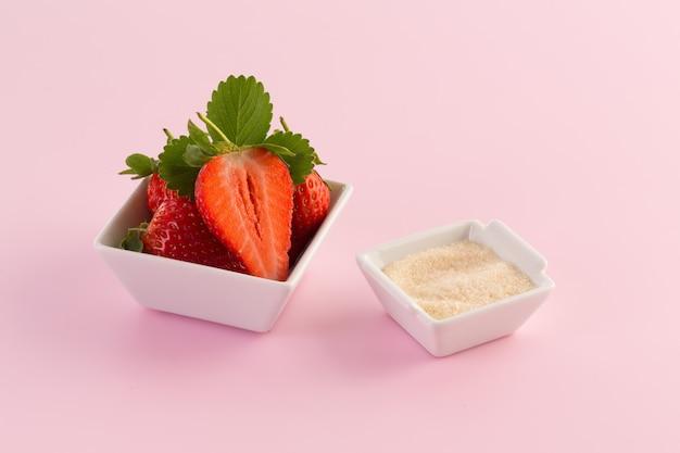 Frische erdbeere und zucker auf rosa hintergrund