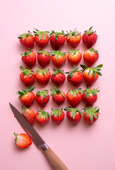 Frische erdbeeren arrangiert auf einem rosa tisch