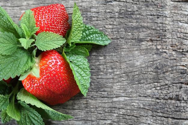 Frische erdbeeren auf hölzernem hintergrund whith tadelloses blatt