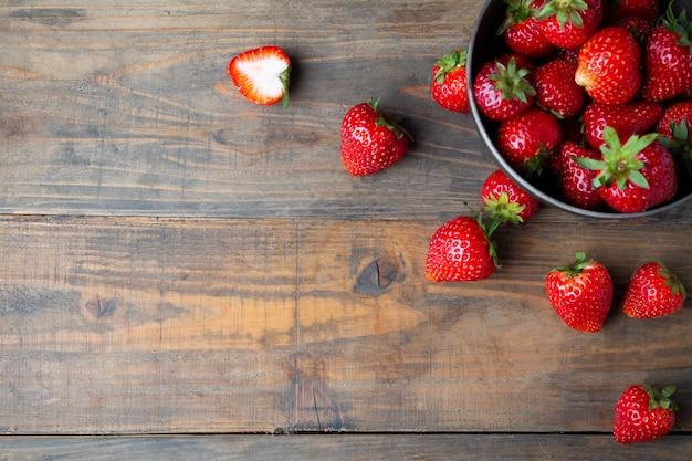 Frische erdbeeren auf holztisch.