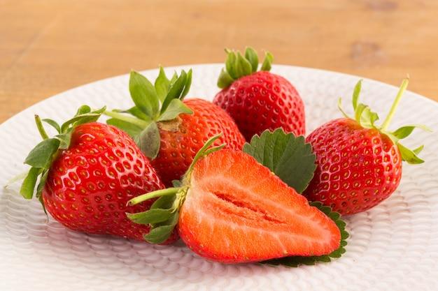 Frische erdbeeren auf weißem teller auf holztisch