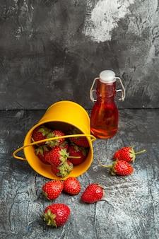 Frische erdbeeren der vorderansicht im korb auf dunklem boden