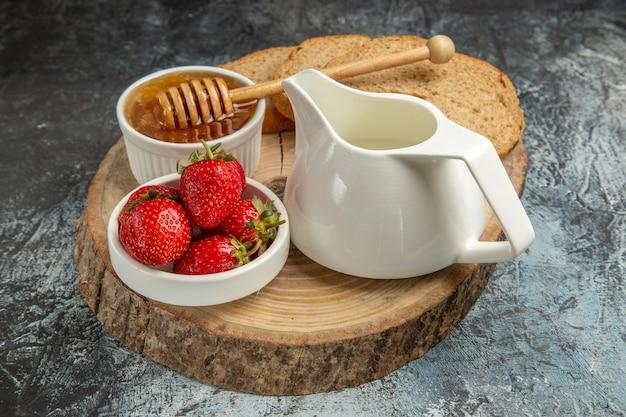 Frische erdbeeren der vorderansicht mit honig auf süßem gelee der frucht der dunklen oberfläche