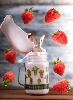 Frische erdbeeren fallen in ein glas, um einen köstlichen erdbeersmoothie zu machen. holzwand