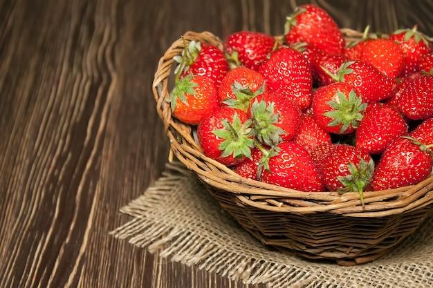 Frische erdbeeren im weidenkorb auf altem braunem hölzernem hintergrund, kopienraum