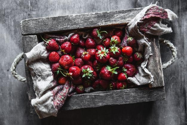 Frische erdbeeren in der box auf hölzernem weinlese-tisch
