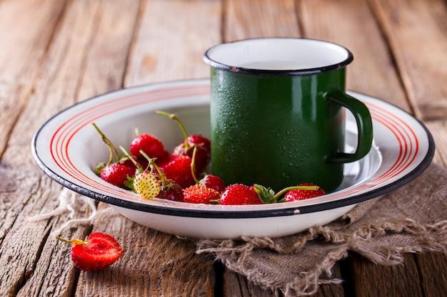 Frische erdbeeren in der eisenschale mit einer tasse milch