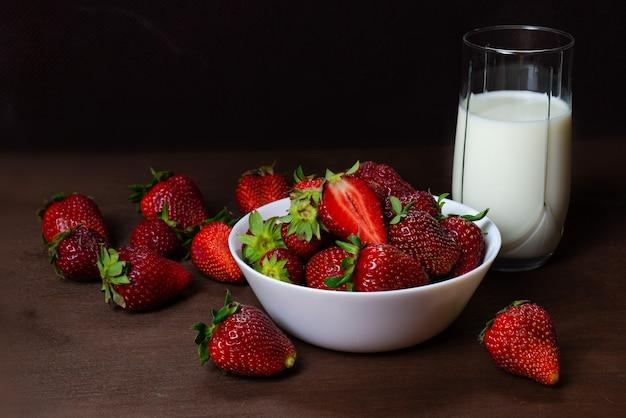 Frische erdbeeren in der keramischen schüssel und in einem glas milch auf dunklem hölzernem hintergrund