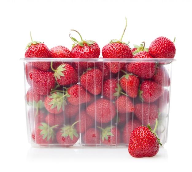 Frische erdbeeren in der plastikkastenfrucht auf weiß