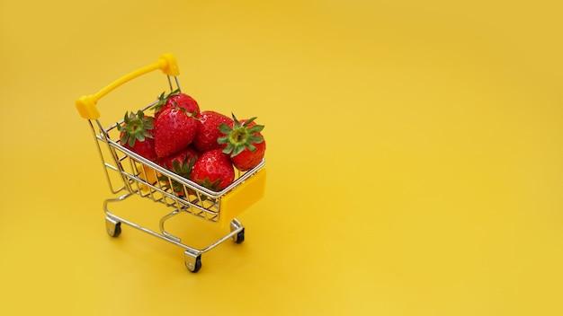 Frische erdbeeren in einem einkaufswagen auf einem hellen gelben hintergrund