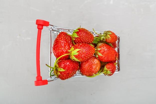 Frische erdbeeren in einem einkaufswagen auf grauem hintergrund. horizontales foto