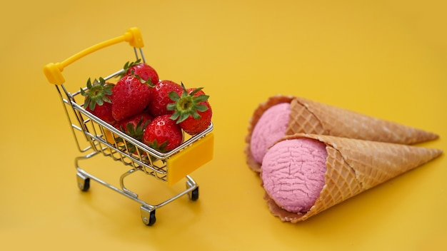 Frische erdbeeren in einem einkaufswagen und erdbeereis