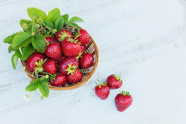 Frische erdbeeren in einem korb auf rustikaler hölzerner tischoberansicht