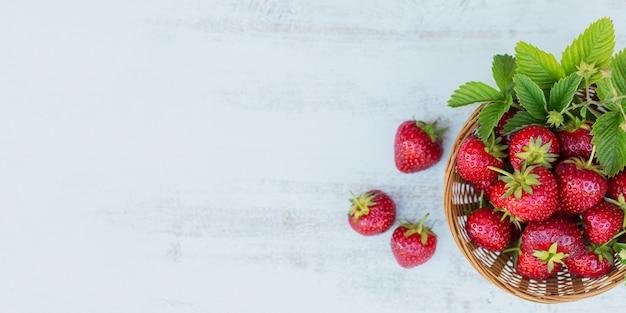 Frische erdbeeren in einem korb auf rustikaler holzwand draufsicht. gesundes essen auf weißem holztischmodell. köstlicher, süßer, saftiger und reifer beeren-bacgroung mit kopierraum für text.
