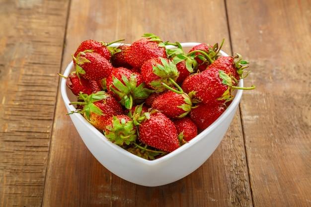 Frische erdbeeren in einem teller in herzform vor einem hölzernen hintergrund.