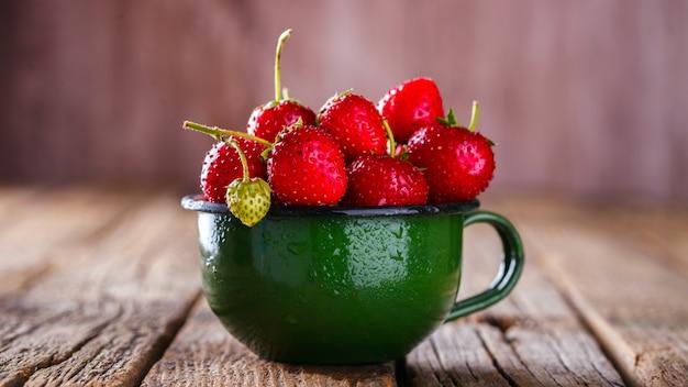 Frische erdbeeren in einer grünen emaille-tasse